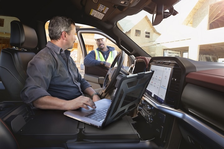 A man using a laptop on the interior work surface in a 2021 Ford F 1 50