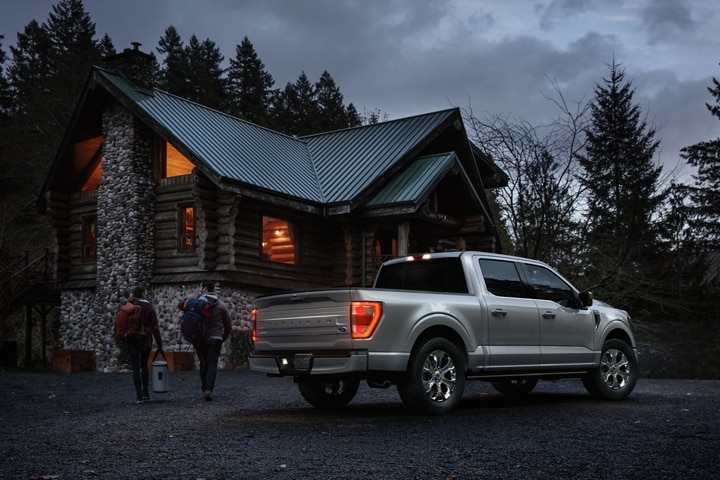 Two people approaching a remote cabin with a 2021 Ford F 1 50 Platinum parked nearby
