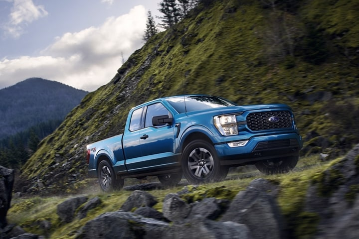 A 2021 Ford F 1 50 rounding a curve on an off road trail in the mountains