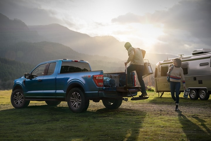 A couple loading camping gear into the bed of their 2021 Ford F 1 50 near their campsite