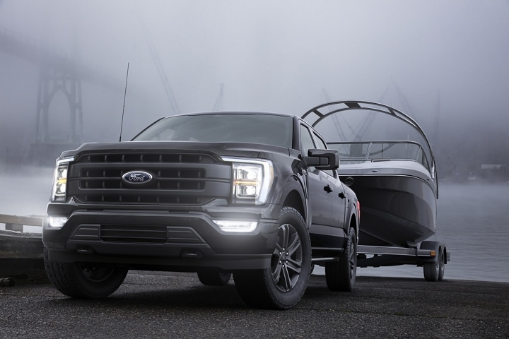 A 2021 Ford F 1 50 parked with its L E D headlamps on at a boat ramp at dusk