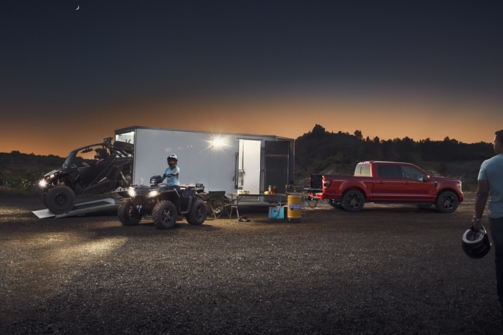 A trailer hauling off road vehicles being lit up by the 2021 Ford F 1 50 zone lighting