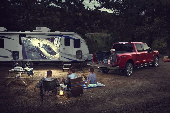 A family watching a movie being projected onto a screen outside a trailer near a 2021 Ford F 1 50