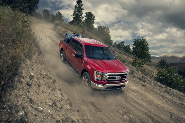 A 2021 Ford F 1 50 being driven down an dirt hill