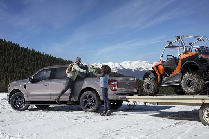 Two people unloading a 2021 Ford F 1 50 in the snow